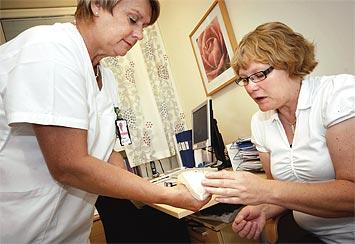 Eva Gillsparr visar Karin Svensson protesen med klister.