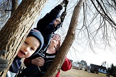 Lena Källman kollar när Eil Larsson och Elias Brolinklättrar. Hon planterade busken som blev ett träd.
