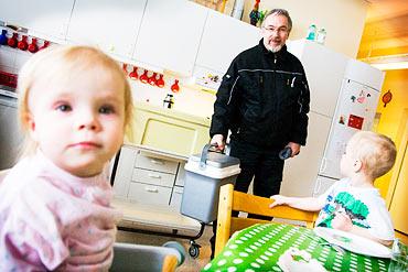 Vaktmästaren Gösta Widell kommer med matboxar till Småbarnsskolan Mullvaden, där Sally, 1 år och Vilmer, 3 år, väntar på att få äta.
