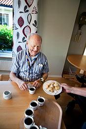 Evert Rydman blir bjuden på nybakade småkakor. Han är med och påverkar boendet genom att delta i den pedagogiska gruppen.