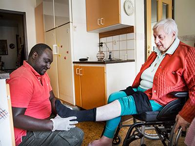 Ebrima Samateh hjälper Naima Elisabeth Fransson med stödstrumporna.