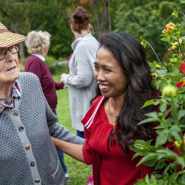 Emily Palenzuela visar blommorna i sin trädgård för Gudrun Borefelt.