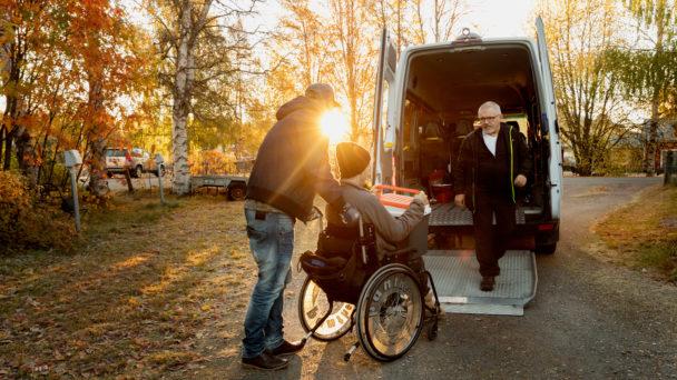 Personliga assistenten Andreas Nilsson, till vänster, och chauffören Lasse Vestman hjälper Simon Moritz in i bussen för avfärd mot dagverksamheten.