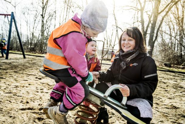 Barnskötaren Camilla Edlund gungar Agnes Andersson och Michelle Kihl.