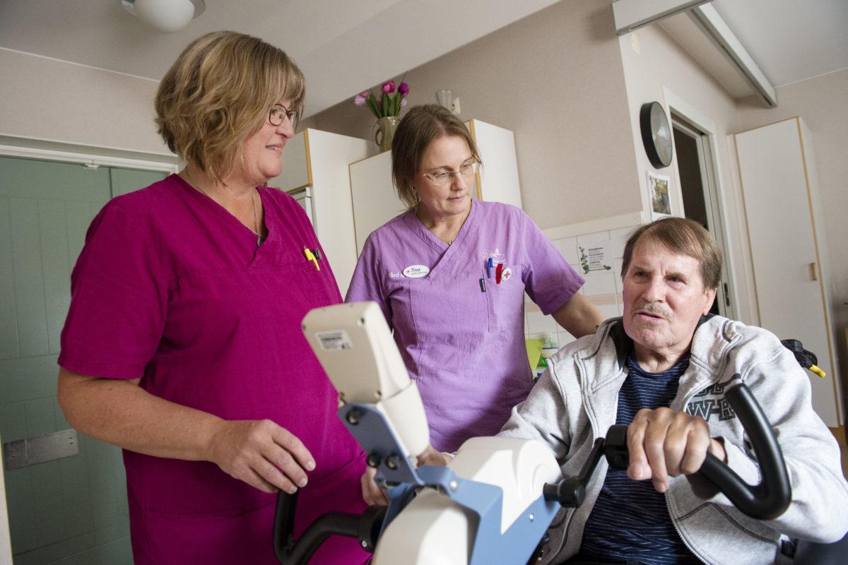Undersköterskorna Marie Toivonen och Tina Högman hjälper Lars Larsson i hans rehabiliteringsträning.