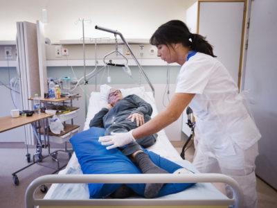Olga Svensson hjälper Gunilla Ericsson, som just fått en avlastande kudde under benen.