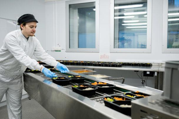 Köksbiträdet Andreas Bergström lägger upp mat.
