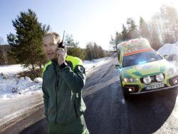 Mats kommunicerar med SOS Alarm. I ambulansen bakom vårdas ett barn med andningssvårigheter.