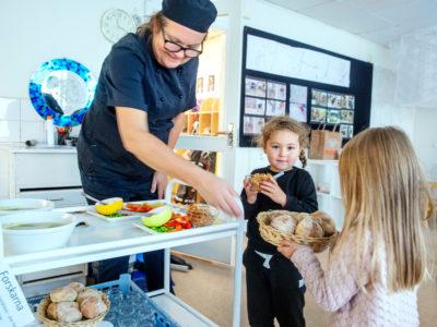 Leila Dahlborg serverar lunch till Esther-Ray och Lykke.
