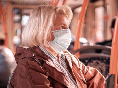 kvinna med munskydd på buss