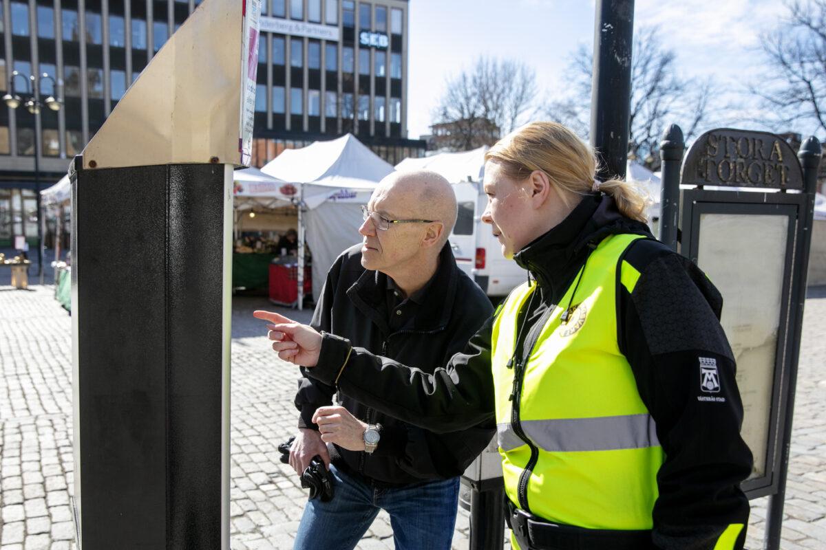 Michaela Ekström hjälper Per Hultén att förstå parkeringsautomaten.