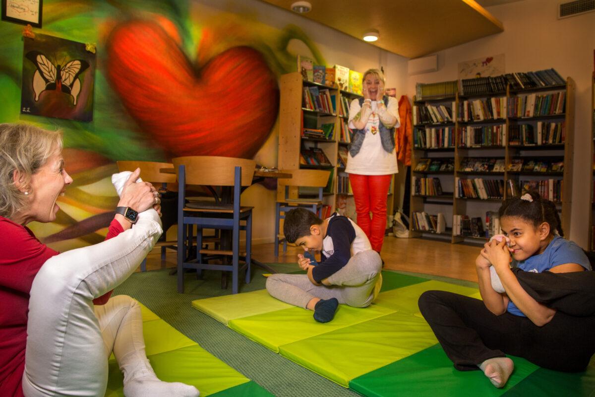 Dags för yoga! Eleverna mjukar upp med att försöka lukta på sin egen fot. Reda och Madonna tycker att övningen är skojig.
